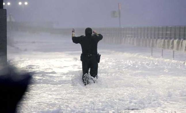Un agent de la Policia municipal de Sant Sebastià envoltat per l'onatge al Paseo Nuevo, que continua tancat pel consistori donostiarra en previsió de les fortes ràfegues de vent al litoral i onades de fins a 7 metres durant la plenamar.